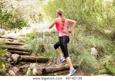 Blonde athlete running up wooden stairs in the nature