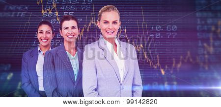 Smiling young businesswomen in a line against stocks and shares