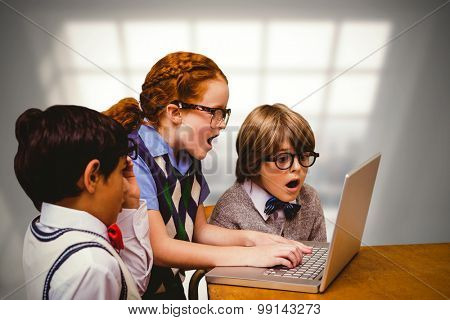 Pupils using laptop against room with large window showing city