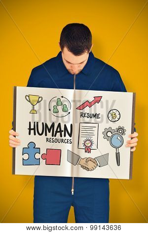 Manual worker showing a book against yellow background with vignette
