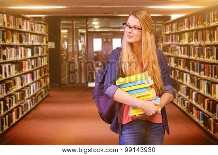 Pretty student in the library against entrance of the college library