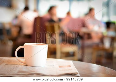 Coffee Cup Over Newspaper On The Table With People In Coffee Shop As Blur Background