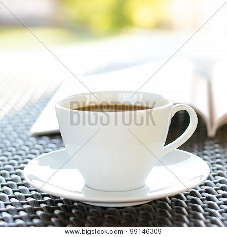 Coffee Cup With Book On Wicker Table