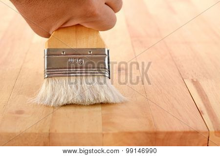 Hand With Brush On Wood Table Top