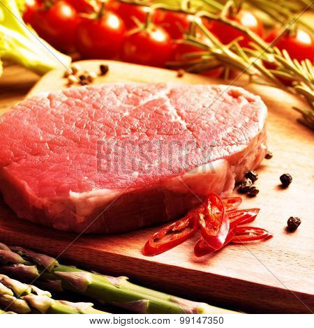 Raw Steak with green asparagus on wooden board. Filtered image: vintage effect.