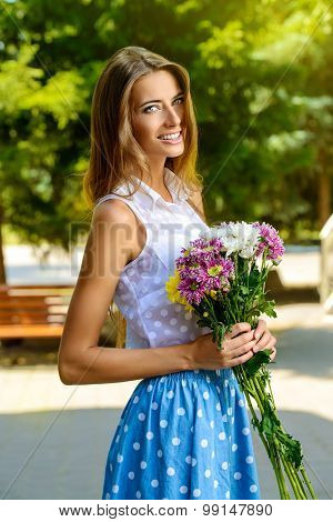 Happy smiling girl with bouquet of flowers standing outdoor. Summer day.