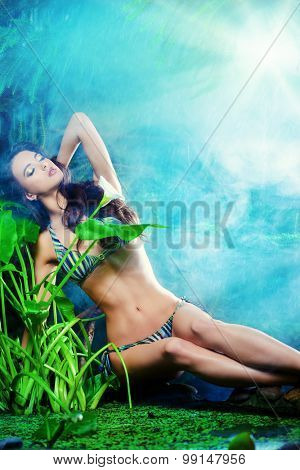 Beautiful slim girl sitting by the pond in the rainforest. Beauty, fashion. Spa, healthcare. Tropical vacation.