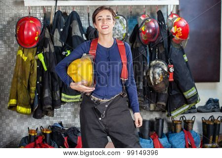 Portrait of confident female firefighter holding helmet while standing at fire station