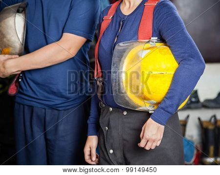 Midsection of male and female firefighters holding helmets at fire station