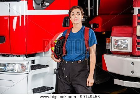 Portrait of confident firewoman holding helmet while standing against firetruck at station