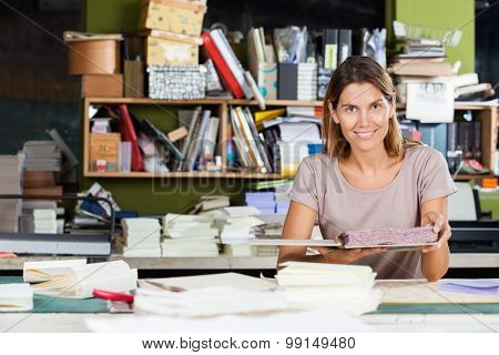 Portrait of confident mid adult female worker holding spiral book in factory