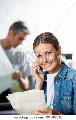 Portrait of smiling mid adult worker holding papers while using cell phone in factory