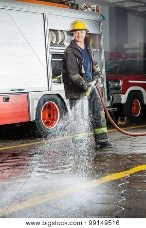 Portrait of smiling fireman spraying water on floor during training at fire station