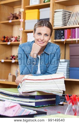 Portrait of smiling female customer with hand on chin leaning on stacked papers in store