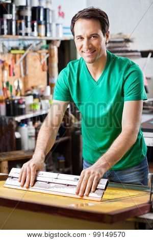 Portrait of confident mid adult worker using squeegee on a silkscreen