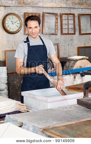 Portrait of confident worker stirring pulp and water with wood in paper factory