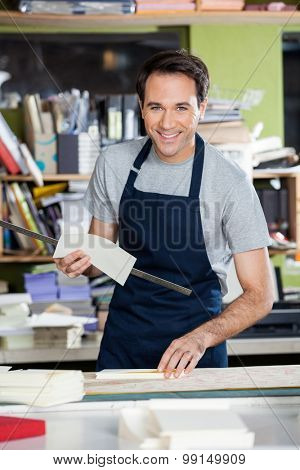 Portrait of smiling mid adult male worker working at table in paper industry