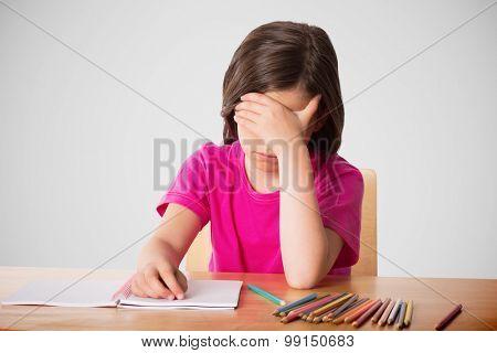Cute pupil working at her desk against grey vignette