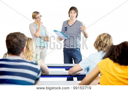 Male student explaining notes besides teacher in the class