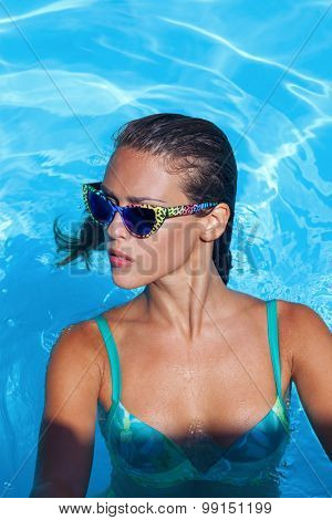 young brunette in the water wtih sunglasses