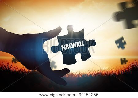 The word firewall and businessman pointing with his finger against orange sunrise