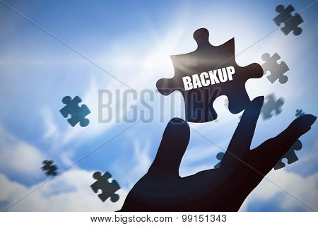 The word backup and hand showing against blue sky