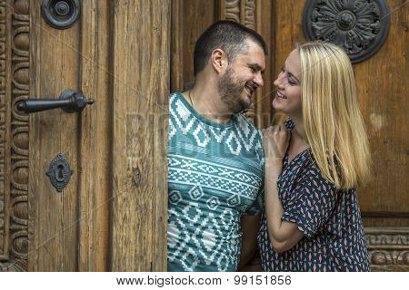 Young couple in love hugging while standing next to an ancient doors.