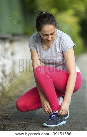 Young sporty woman tying running shoe laces in park in beautiful summer day. Sport fitness model caucasian ethnicity training outdoors. Workout in a Park.