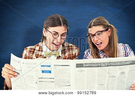 Geeky hipsters reading the newspaper against blue chalkboard