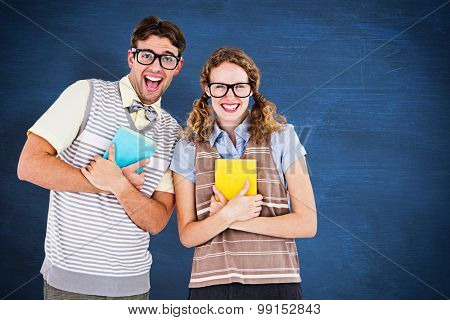geeky hipster couple holding books and smiling at camera against blue chalkboard