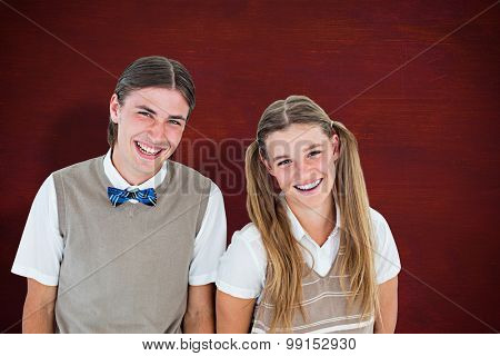 Smiling geeky hipsters looking at camera against desk