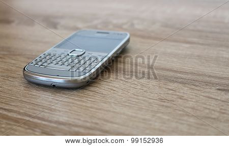 Silver Mobile Phone On The Wooden Table