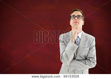 Geeky happy businessman thinking with hand on chin against desk