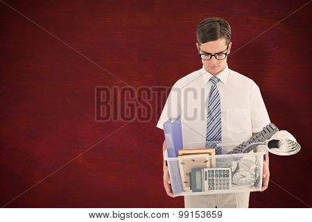 Fired businessman holding box of belongings against desk