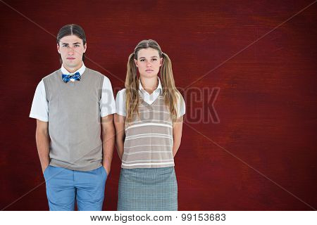 Unsmiling geeky hipsters looking at camera against desk