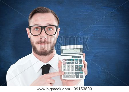 Geeky businessman pointing to calculator against blue chalkboard