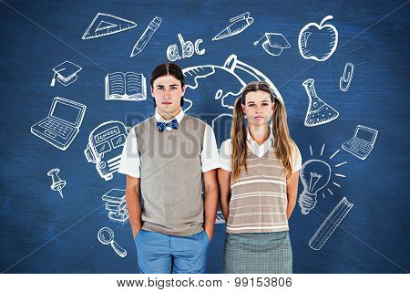 Unsmiling geeky hipsters looking at camera against blue chalkboard