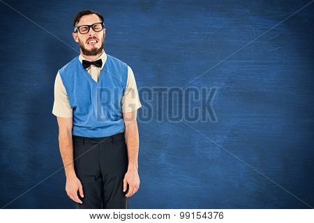 Geeky hipster pulling a silly face against blue chalkboard
