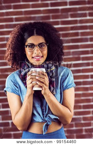 Portrait of smiling attractive hipster with take-away cup against red brick background