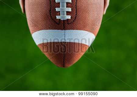 Close up view of upheld football on american football field