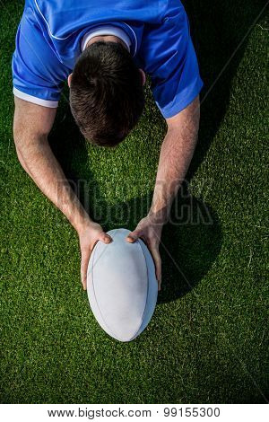 Upward view of a rugby player scoring a try
