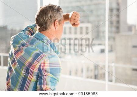 Troubled casual businessman leaning against window in the office