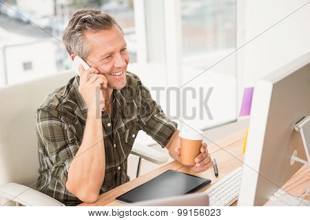 Smiling casual businessman having a phone call in the office