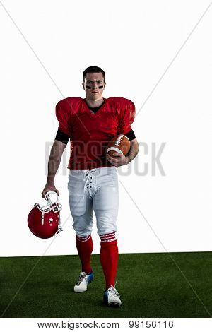 Portrait of american football player walking and holding football and helmet on american football field