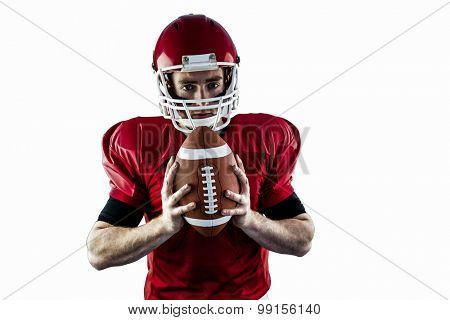 Portrait of focused american football player holding football against white background