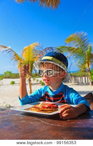 little boy eating in beach cafe outdoors