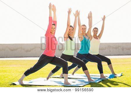 Portrait of smiling sporty women doing warrior pose in yoga class in parkland