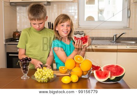 Portrait of children eating fruits. Boy and girl in the kitchen. Funny playful kids cooking together