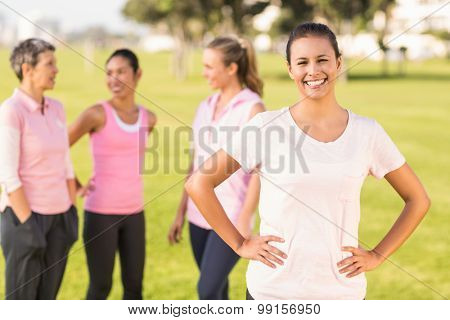 Portrait of smiling brunette wearing pink for breast cancer in front of friends in parkland