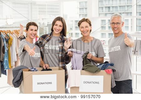 Portrait of smiling volunteers with donation boxes in the office